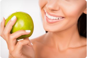 Close Up Portrait Of Woman With Healthy Teeth Holding An Apple